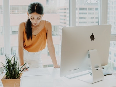 female founder leaning on her desk with computer, private equity, entrepreneur