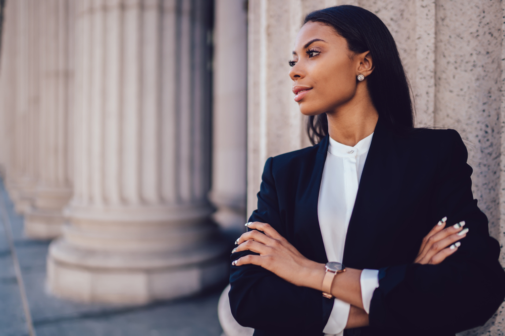 Female African American banker dressed in elegant black suit folding hands and looking on side standing against office building, dress code