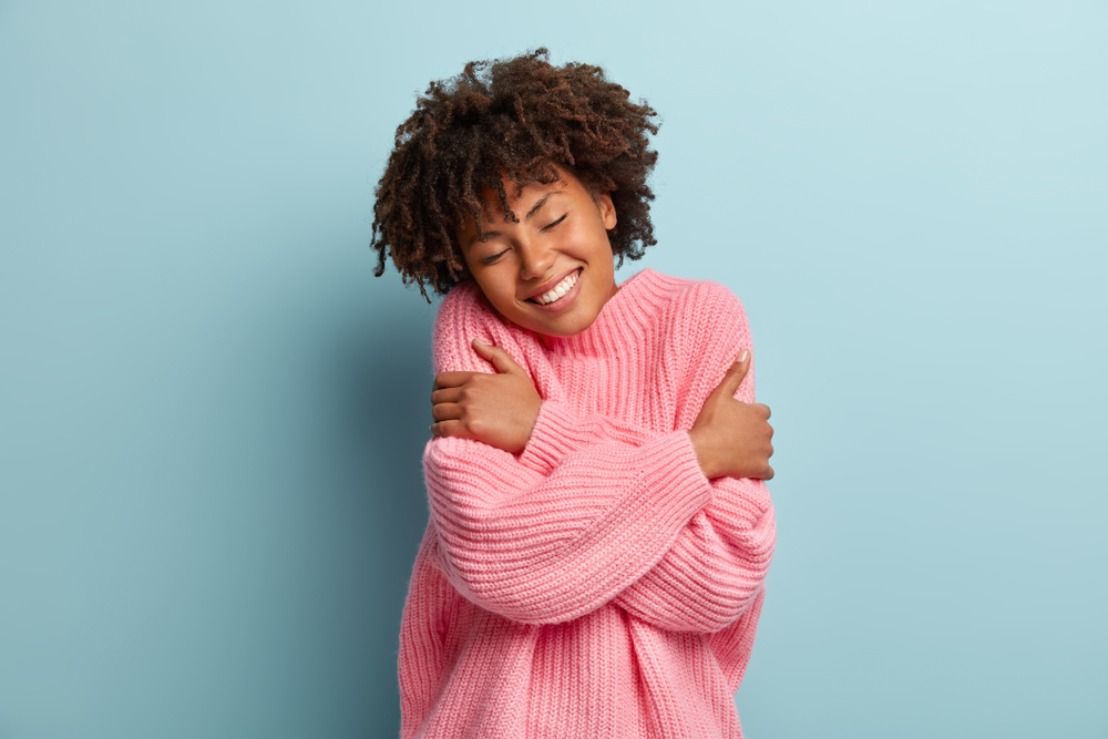 Love yourself concept. Photo of lovely smiling woman embraces herself, has high self esteem, closes eyes from enjoyment, likes her new comfortable soft pink sweater, tilts head, stands indoor. self care