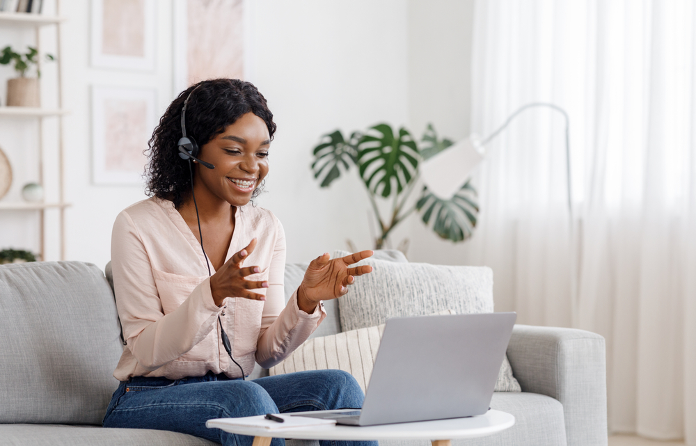 Video Conference. Smiling african woman having web call on laptop at home, talking at camera while sitting on sofa in living room, flexible working